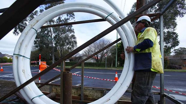 Workers lay pipes for fibre optic cables in Armidale.