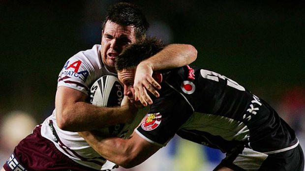 Jamie Lyon of Manly is tackled by Shaun Berrigan of the Warriors.