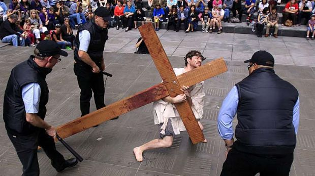 Three men playing security officers taunt another man playing Jesus Christ during a modern interpretation of the ...