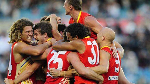 Day in the sun ... Gold Coast players mob each after their surprise three-point victory over Port Adelaide at AAMI Stadium.