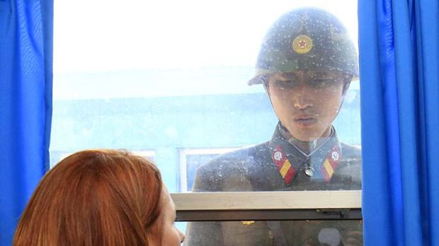 Drawing the line ... the Prime Minister, Julia Gillard, and a North Korean soldier in the border village of Panmunjom.