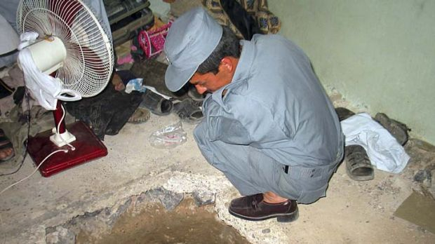An Afghan policemen takes a look at the opening of the tunnel.