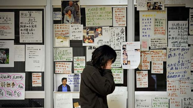 A survivor next to a message board in Rikuzentakata.