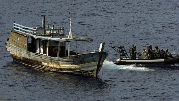 A Navy team leaves a boat just off Christmas Island, but  the Gillard government's efforts to send asylum seekers to ...