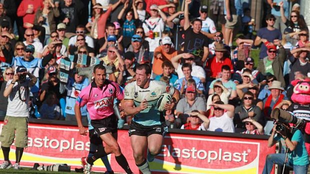 Poles apart ... Cronulla and Blues captain Pual Gallen rumbles over for a try yesterday in a game that epitomised his ...