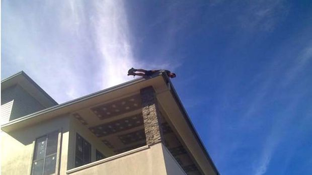 A photo posted on Facebook of a man planking on a roof.
