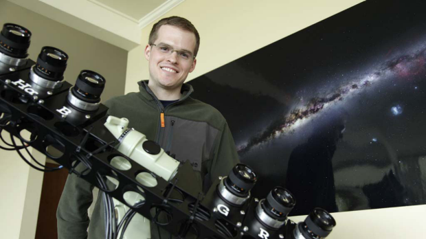 Nick Risinger poses with the rack of six synchronized astrophotography cameras he used to create the photograph on the ...