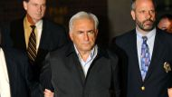 IMF head Dominique Strauss-Kahn (C) is taken out of a police station in New York on May 15, 2011. Strauss-Kahn was ...