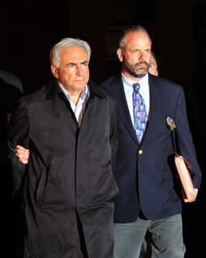 A handcuffed Dominique Strauss-Kahn (left) is taken from a police station in New York. Strauss-Kahn was charged Sunday ...