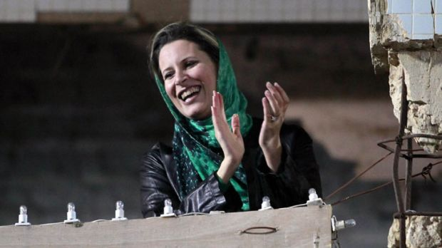Seeking refuge ...  Muammar Gaddafi's daughter Aisha supports a pro-government rally last month. She has reportedly fled ...