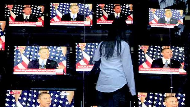 An Egyptian woman watches Mr Obama's address in Cairo.