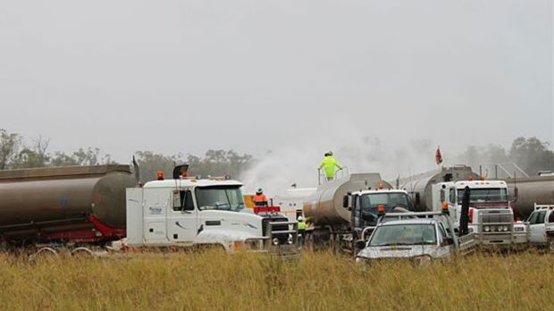 Workers try to stem the leak of water and gas from a well near Dalby this morning.