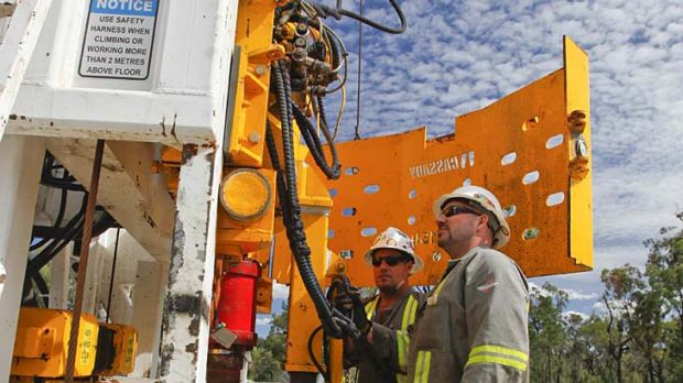 Workers examine a rig at a Queensland coal seam gas site.
