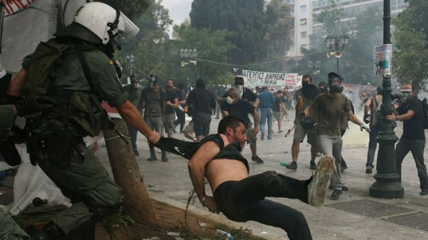 Tumult ... protesters clash with riot police in central Athens as thousands of people besieged the Greek parliament to ...