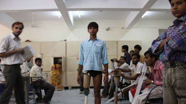 19-year-old Tileshwar Prasad admires his new Jaipur Foot and Stanford-Jaipur knee. The new prosthetics cost a total of ...