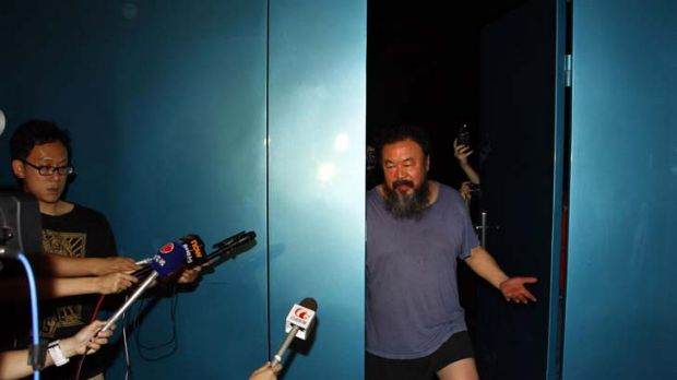 Considerably thinner ... Chinese artist Ai Weiwei waves from his studio after being released by Chinese police from ...