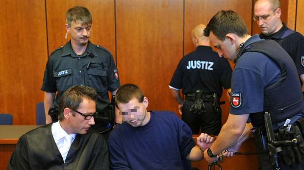 Guilty ... a police officer takes off the handcuffs of defendant Jan O, whose face has been blurred in accordance with ...