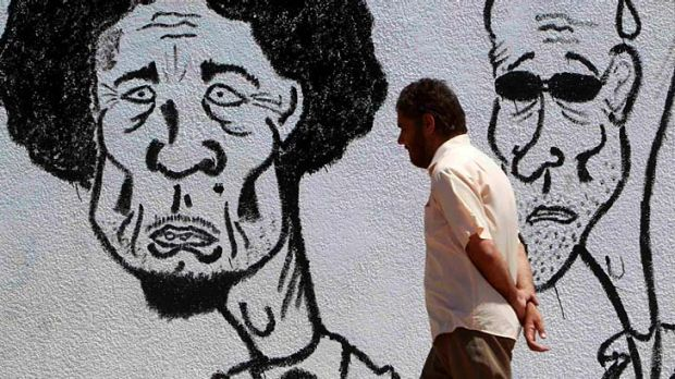 A man walks past caricatures of Libyan leader Muammar Gaddafi (left) and his son Saif near a courthouse in Benghazi1.