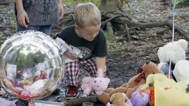 Yadiel Perez, 3, of Kissimmee, Florida, places a teddy bear at a memorial to Caylee Anthony  in Orlando.