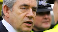 Britain's Prime Minister Gordon Brown speaks to a police officer in Cockermouth, northern England in a November 21, 2009 ...