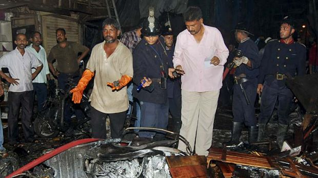 Bomb blast ... policemen inspect the site of an explosion at Zaveri Bazaar.