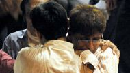 Friends console a man (R) who lost his brother, outside an hospital casualty in Mumbai on July 13, 2011.