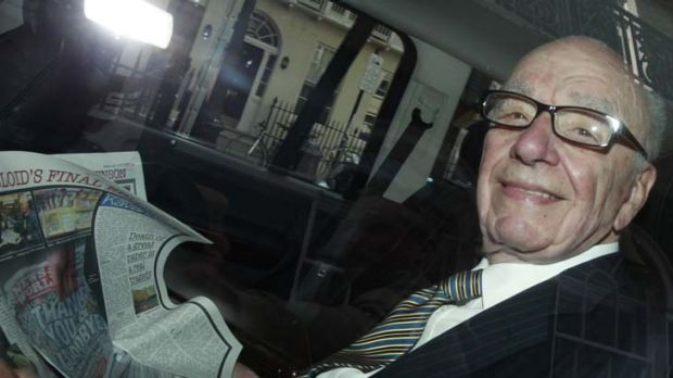 All smiles ... Rupert Murdoch holds a copy of <em>The Sun</em> as he is driven away from his flat earlier this week.