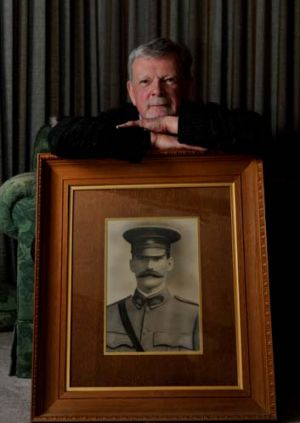 John Sheridan with a portrait of his grandfather Captain Thomas Sheridan who died in the World War I Battle of Fromelles.