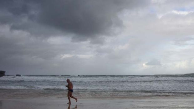 Calm before the storm ... an early morning swimmer braves the weather on deserted Bondi Beach. Strong winds and heavy ...