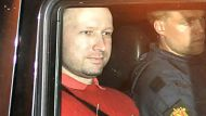 Bomb and terror suspect Anders Behring Breivik (red top) leaves the courthouse  in a police car  in Oslo on July 25, ...