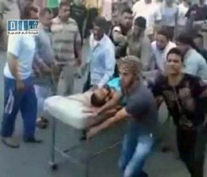 Hama residents rush an injured man to hospital.