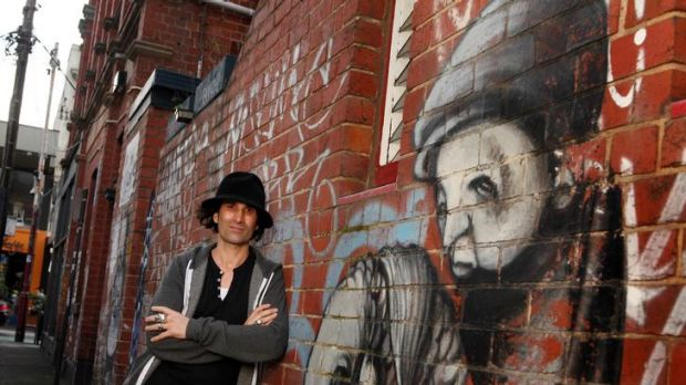 Stormie Mills with some of his Melbourne street art in Prahran.
