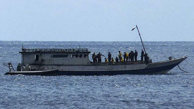 An Australian Navy boat comes alongside a boat carrying 50 asylum seekers after it arrived at Flying Fish Cove on ...