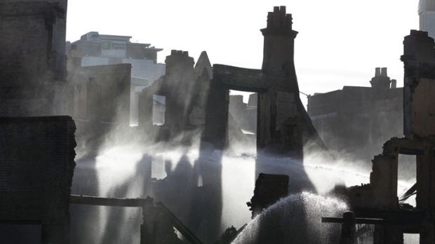 A crumbling nation ... a firefighter sprays water on a furniture store set on fire by rioters in Croydon, south London.