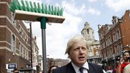 London Mayor Boris Johnson carries a broom in Clapham Junction, in south London August 9, 2011. British Prime Minister ...