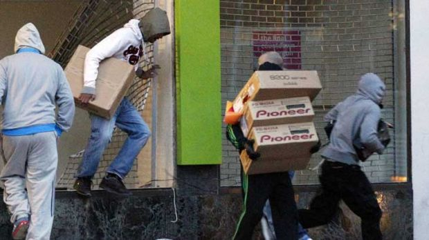 Looters carry boxes out of a home cinema shop in central Birmingham.