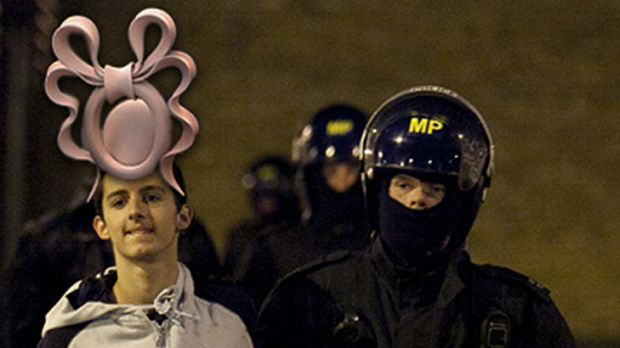 Fashion grab ... A riot suspect is given Princess Beatrice's infamous royal wedding hat.