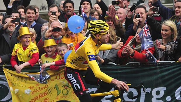 Cadel Evans greets fans during the parade in Melbourne yesterday.