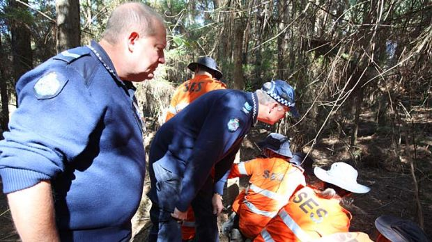 Police and SES volunteers work their way through dense bushland at Beerwah on Queensland's Sunshine Coast in the search ...
