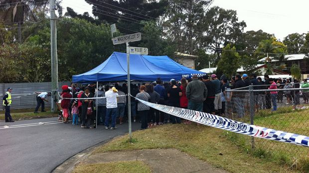 A crowd gathers at the scene of the fire at Logan this morning.