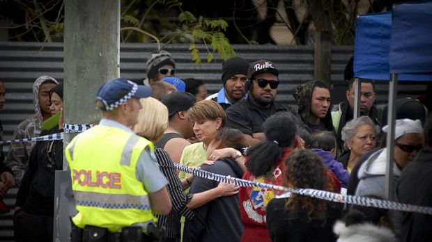 Premier Anna Bligh with family and friends of the 11 people who are believed to have been killed at a house fire ...