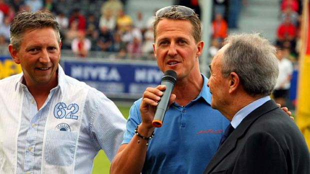 Michael Schumacher (centre) speaks during a charity soccer match between a team of Formula 1 drivers and a team of ...