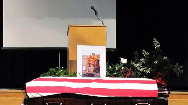 Loyal to the end ... Hawkeye lies beside the coffin of US Navy SEAL Jon Tumilson during his funeral.