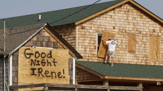 Race against time ... a man boards up a house as 200,000 North Carolina residents were ordered to leave after the storm ...
