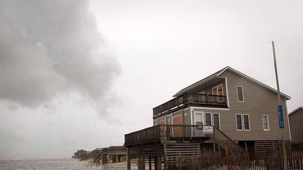 Tide rolls up under a home as wind, rain and tidal surge from Hurricane Irene begin to be felt along the Outer Banks in ...