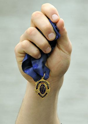 A Brownlow Medal in Gary Ablett's hand.