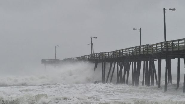 Waves pound a fishing pier in Nags Head, North Carolina.