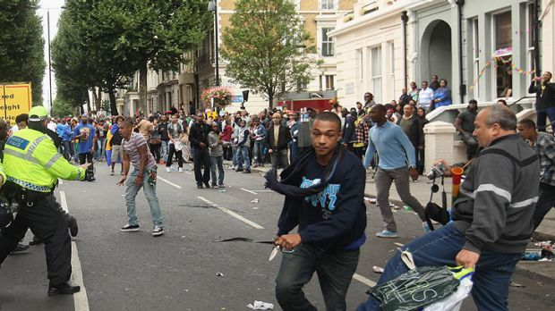 A man flees carrying a knife as a bystander tries in vain to trip him up after a stabbing at London's Notting Hill Festival.