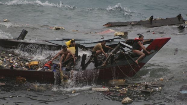 Asylum seekers cling to the wreckage of their boat as it takes water near Flying Fish Cove on Christmas Island last December.