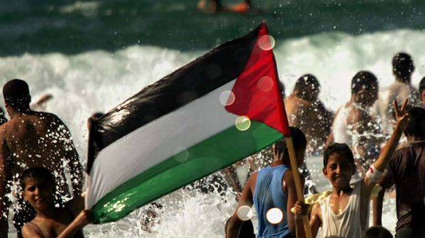 """There is also a sense of foreboding"" ... Palestinian children hold the national flag as bathers enjoy the Mediterranean ..."